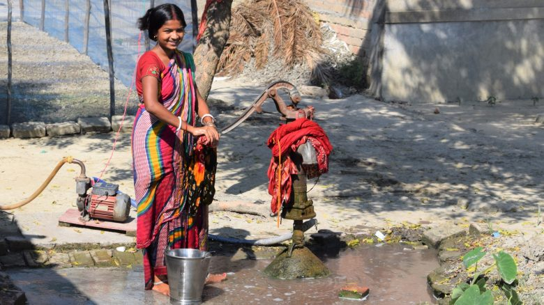 Indian women working a water pump
