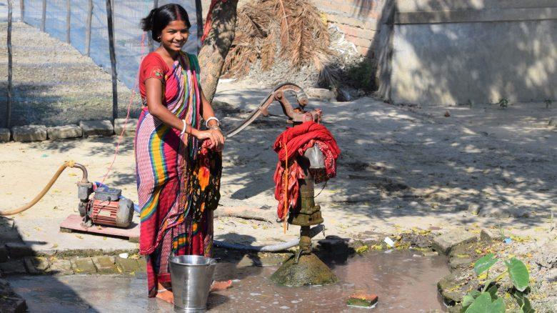 Indian women working a water pump