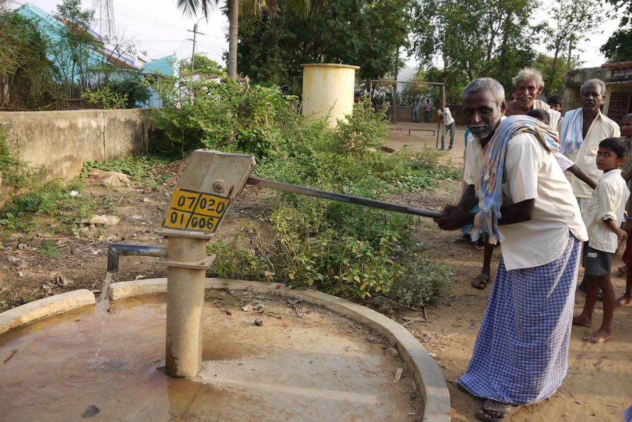 Indian man working the water pump